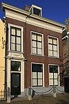 foto van Pand van parterre en verdieping onder schilddak met topschoorsteen. Eenvoudige lijstgevel van drie vensterassen, waarvan de linker, die de ingangspartij bevat, als risaliet is opgevat