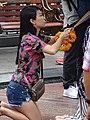 Woman Making an Offering - Bangkok - Thailand (34533758512).jpg