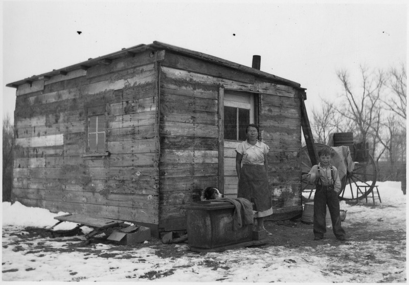 File:Women and child in front of cabin made of what appears to be scrap lumber - NARA - 285849.tif