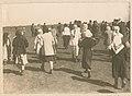 Women walk across a field (9315805132).jpg