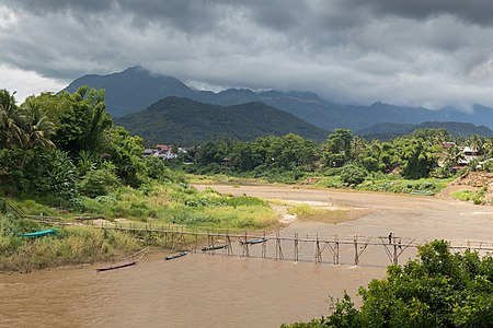 Landscape with a wooden footbridge crossing the Nam Khan river, where two workers are working at the consolidation of this structure, holding a big beam under a cloudy sky during the monsoon, in Luang Prabang, Laos