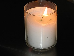 A lit Yahrtzeit candle, a candle that is lit o...