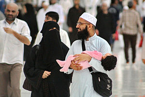 Religion and children - A young Muslim couple and their toddler at Masjid al-Haram, Makkah, Saudi Arabia.