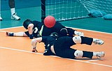 Two goalball players stretch to the left to stop the ball.