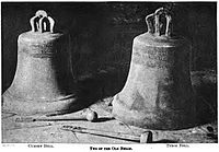 Two large church bells resting on a stone pavement, each carved with a indistinguishable inscription.