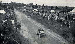 1903 Gordon Bennett Trophy. De Knyff passes Winton repairing his car.jpg