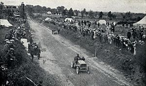 Castledermot - 1903 Gordon Bennett Trophy. René de Knyff, driving his Panhard to second place, passes Alexander Winton repairing the Winton Bullet 2 on the first lap.