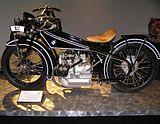 A shiny black Art Deco motorcycle of 1923 with a BMW logo on the gas tank and a boxer twin engine.