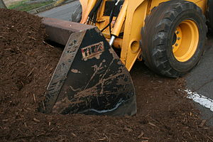Skid-steer loader - A John Deere 280 skid loader moving mulch