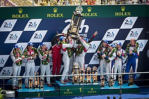 2014 24 Hours of Le Mans - Marcel Fässler, André Lotterer, and Benoît Tréluyer hoist the winners trophy during the podium ceremony