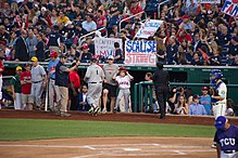 "Baseball fans near the dugout hold signs saying ""Capitol police MVP"" and ""Scalise Strong""."