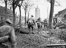 four men in uniform, moving through a tree lined battle damaged street towards a tower in the distance