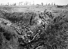 Soldiers wearing helmets and carrying weapons sit in a trench