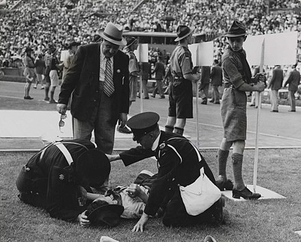 A Boy Scout who fainted in the intense heat was the first 'casualty' of the 1948 Olympic Games. The temperature was noted as 97 degF (36 degC) as the sun blazed down mercilessly. A casualty at the Olympic Games, London, 1948. (7649953728).jpg