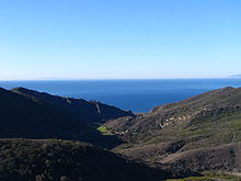 A large valley between arid chaparral-covered hills, opening towards the ocean.