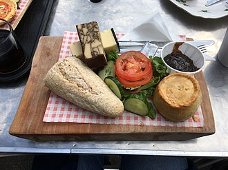Ploughman's lunch - A ploughman's lunch consisting of bread, cheese, butter, salad, a pork pie, and chutney