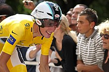 A road racing cyclist in a yellow skinsuit, wearing an aerodynamic helmet. His bicycle is not visible. Spectators watch from the roadside.