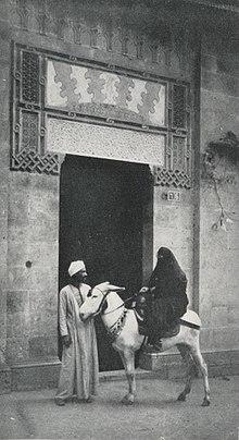 d66b57e24 امرأة مصرية تركب حمارا وصبي يساعدها.