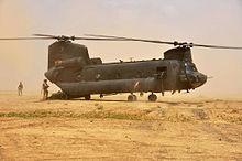 Colour photo of a dark green twin-rotored helicopter on the ground, with considerable amounts of dust in the air around it