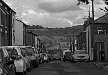 A black and white view of a street with parked cars and terraced brick houses on both sides gently sloping downhill, revealing a view of a hillside with a large brick industrial building on it