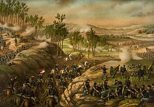 A photograph of Union cavalry moving through a gap to attack Confederate infantry, with Union foot soldiers and cannons firing at the Confedereates on either side of the ridge