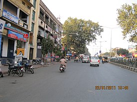 A divided road lined by 3-story shops