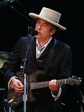 A man behind a microphone stand, wearing a white hat and black suit. The man is playing the guitar and singing into the microphone.