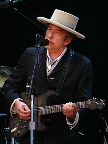 Bob Dylan plays a guitar and sings into a microphone.
