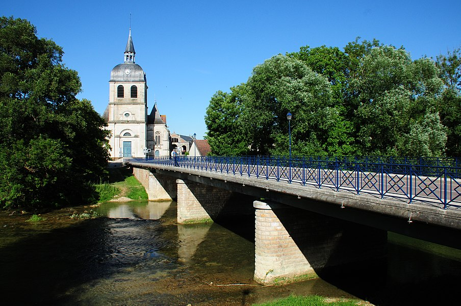 Bridge across the river L' Aube and the church of Dienville
