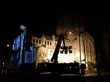 Six lights on a rig lighting up and in front of a Gothic Revival style church building.