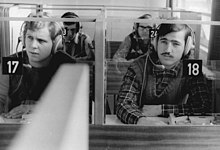 "A black and white picture of two students wearing headphones. One student's booth is numbered ""17"", and the other's is numbered ""18""."