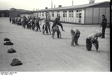 "A line of half-naked prisoners performing ""leap frog"", under supervision of one of the Kapos. In the background the main gate to Mauthausen as well as two wooden barracks are visible."