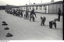 """Rivi puolialastomia vankeja, jotka suorittavat """"harppaavan sammakon"""" yhden kapojen valvonnassa.  Taustalla näkyvät pääportti Mauthauseniin sekä kaksi puuparakkua."""