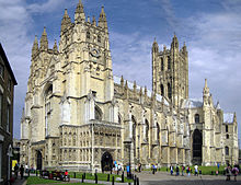 View of the exterior of Canterbury Cathedral on a bright day. The building is of pale stone with three large towers and much ornate Gothic detail. People are entering through a richly sculptured side porch.