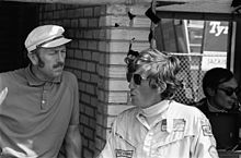 Black-and-white photograph of Colin Chapman on the left and Rindt on the right conversing in the pit lane in front of a brick wall
