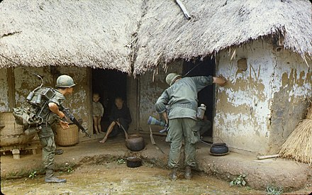 U.S. soldiers searching a village for potential Viet Cong Checking house during patrol.jpg