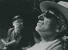 Молодой белый человек в очках читает слепому мужчине постарше в саду