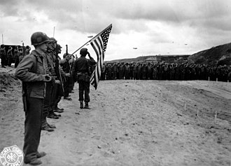 Vierville-sur-Mer - Honor guard with the flag and a bugler during a mass at the site of the first temporary cemetery in Vierville, June 10, 1944.