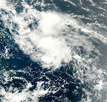A satellite imagery depicting a disorganized mass of clouds across the central Atlantic.