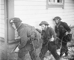 A black and white photograph of three British soldiers advancing beside a wooden house. The lead soldier is carrying a Thompson submachine gun and is peering around the corner of the house, while the other two are carrying rifles.