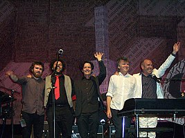 Five men are standing close together on a stage and smiling. Behind the five men is more band equipment and the background contains considerable English text.