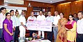 D.V. Sadananda Gowda receiving a cheque of Rs. 19.60 crore as an interim dividend of 20% for the financial year 2014-15 from the Member Traffic, Railway Board and Chairman, Pipava Railway Corporation Limited (PRCL).jpg