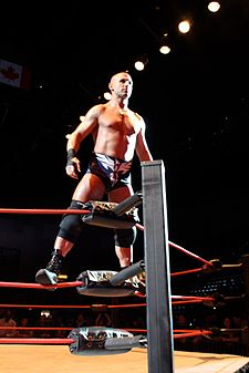 A male with black taped hands wearing black trunks, knee pads, and boots standing on the ropes in a wrestling ring corner.