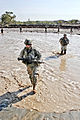 Defense.gov News Photo 101106-A-2911M-045 - U.S. Army Spc. Jacob Phillips front and Spc. Bjorn Goller Hagord cross a river of waist-high muddy water in the Towr Gahr Pass Nangarhar province.jpg