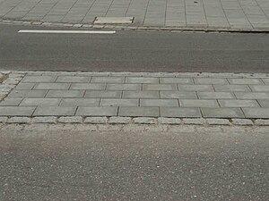 Deutschland Verkehrsinsel Furt Detailsicht Betonplatten Pflastersteinkante.JPG
