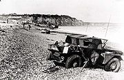 Dieppe's pebble beach and cliff immediately following the raid on August 19, 1942. A scout car has been abandoned.