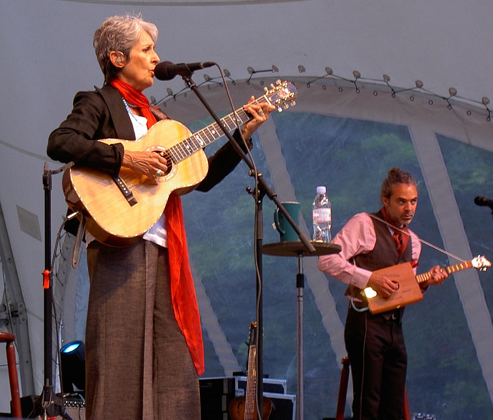 Baez plays outdoors in brown wide-leg pants, white top, brown waistcoat, blue pearls, and a long orange neck scarf. To her left, a male accompanist in a vest plays a small wooden cigar-box-style guitar
