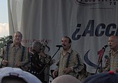 Three aged men dressed with a yellow stripes shirt singing to a microphone.