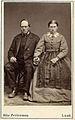 Ett medelålders par poserar sittande på stolar. Löddeköpinge, Harjagers härad i Skåne - Nordiska Museet - NMA.0042846.jpg