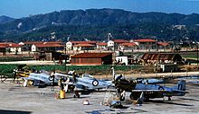 Colour photograph of an airfield. Three single-seat piston-engined propeller aircraft sit in the foreground, as a number of personnel work on the machines which are finished in natural metal with blue, white and red roundels. In the middle distance are a number of makeshift corrogated-iron buildings, while to their rear are several others of more solid construction. In the background rise a number of tree covered mountains.